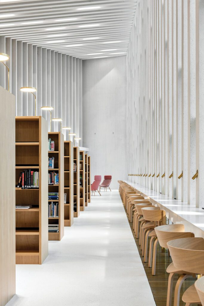 A close up with the geometric forms created by the wood bookshelves and white walls.