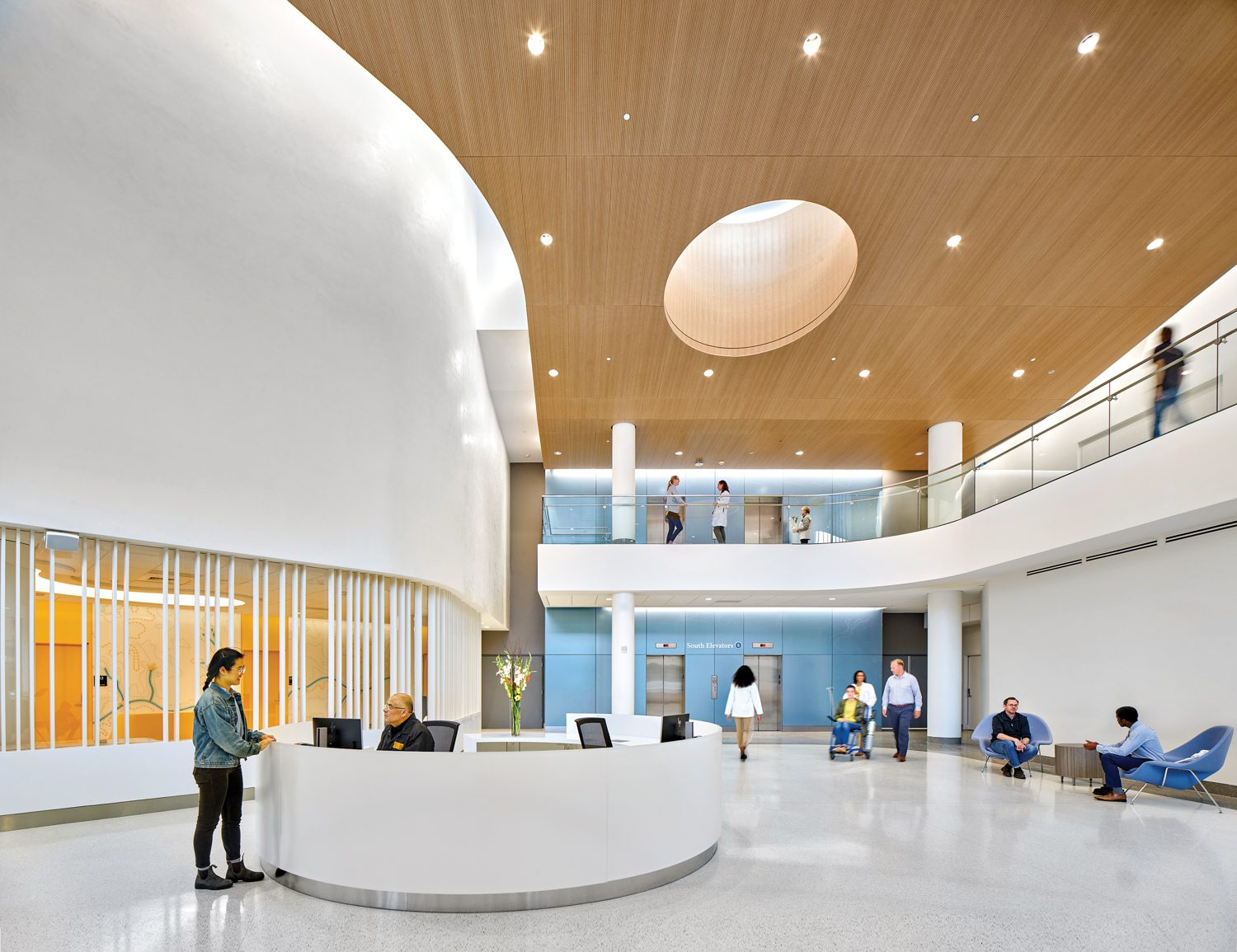 Reception area with a curved white desk and ceiling dotted with small lights.