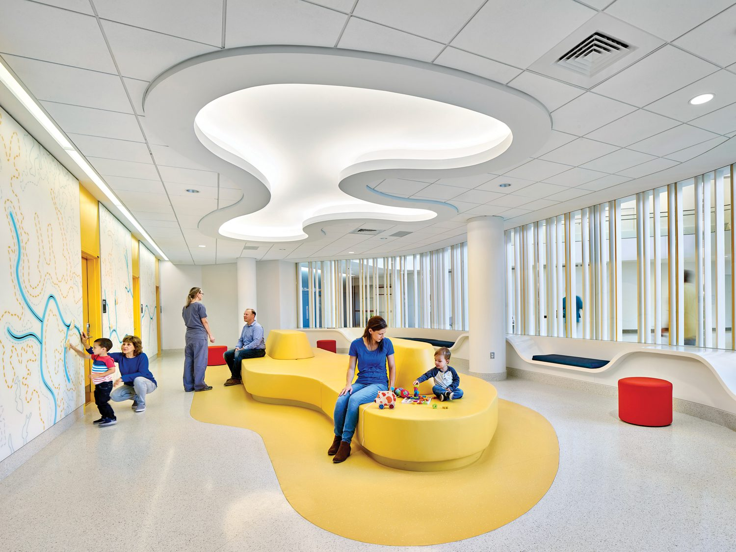 Yellow curved couch beneath a similarly shaped illuminated pattern on the ceiling above in University of Virginia hospital expansion, Charlottesville, by Perkins&Will.