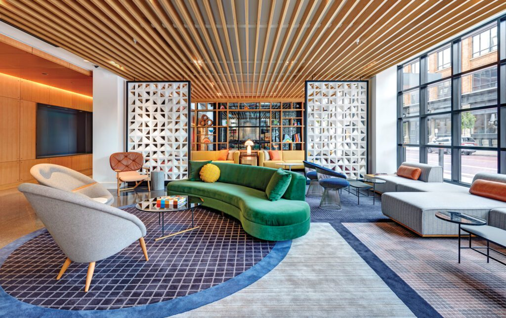 A bright green curved sofa adds a pop of color beneath a ceiling made from wood slats.
