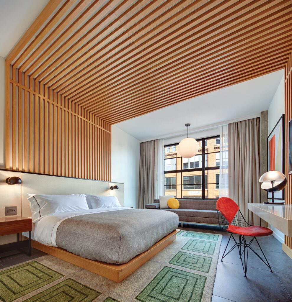 Wood slates line the ceiling and back wall, offering a unique headboard for the bed in this guest room.