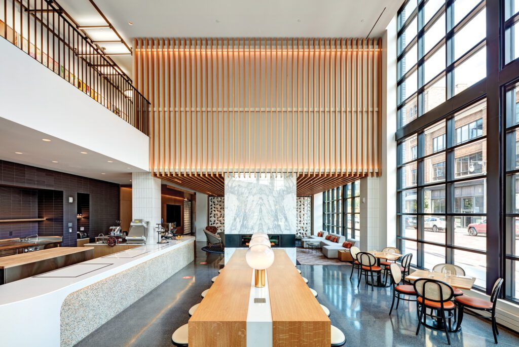 Floor-to-ceiling windows and a long center table create a dramatic dining area.
