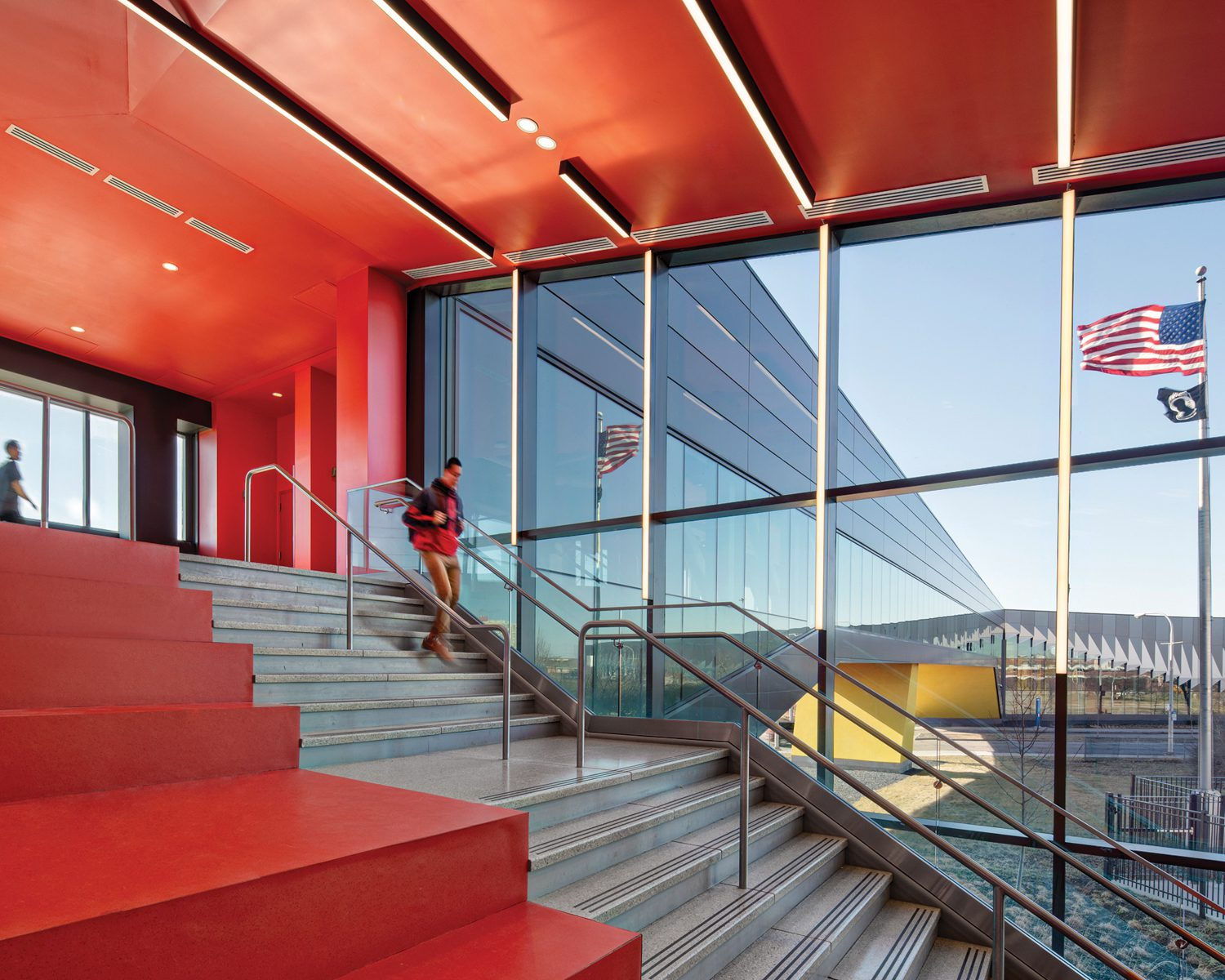 A staircase defined by vibrant red on the floor and ceiling above in Daley College Manufacturing Technology & Engineering Center, Chicago, by JGMA.