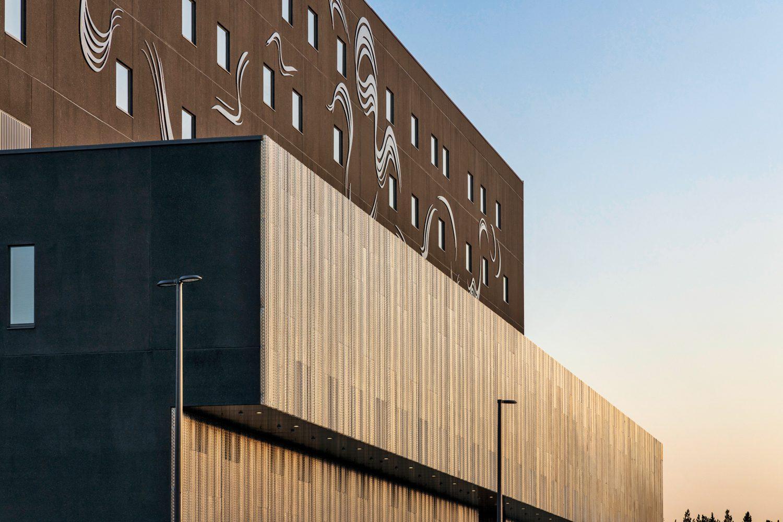 At Hospital Nova in Jyväskylä, Finland, by JKMM Architects, Tiina Pyykkinen's Notes of Lights appears on the facade of iron oxide–tinted precast concrete, under which runs perforated aluminum. Photography: Martin Sommerschield/Kuvatoimisto Kuvio Oy.
