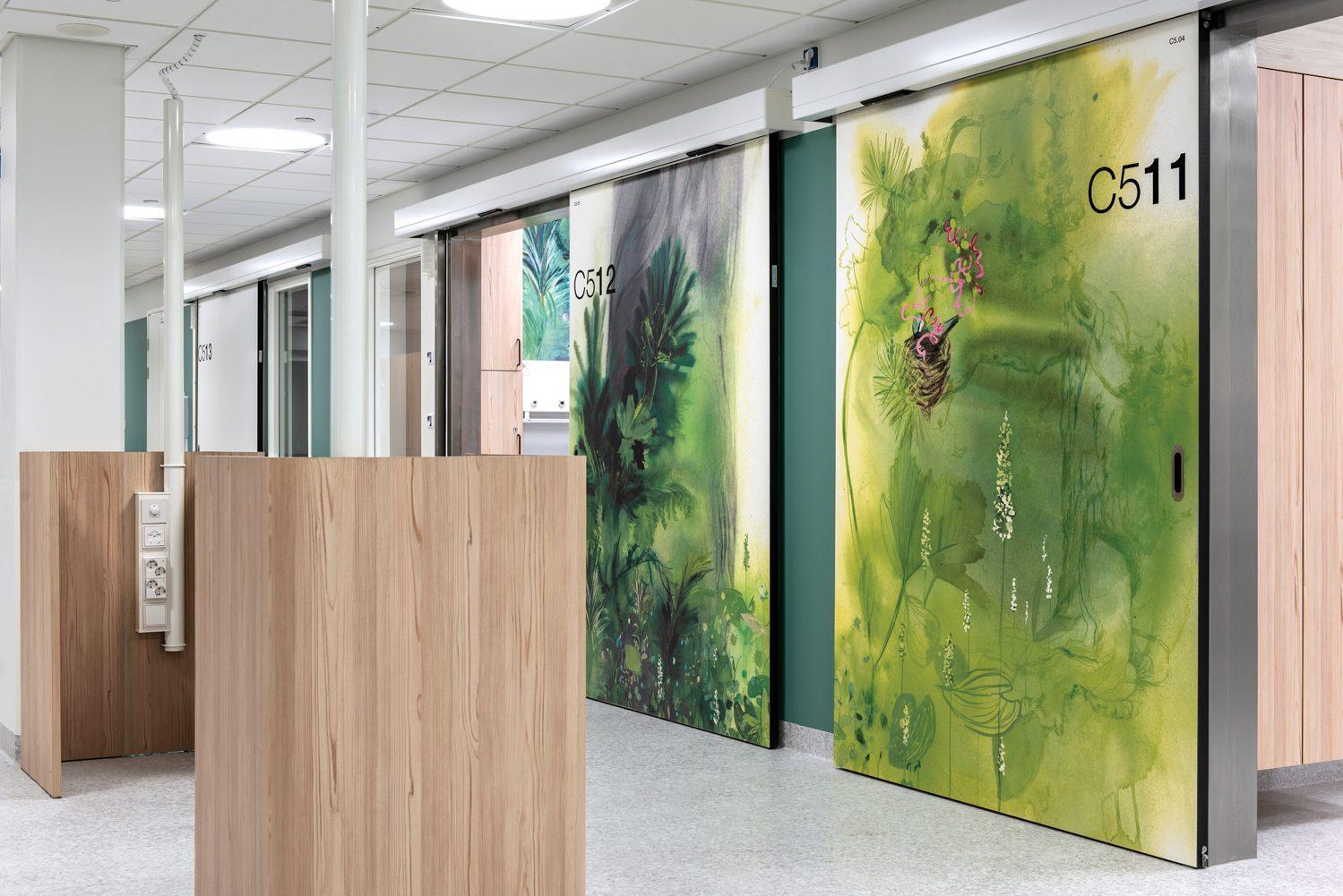 In the patient-room ward, sliding doors hosting Kati Immonen artwork back nursing stations in laminated wood. Photography: Pauliina Salonen.