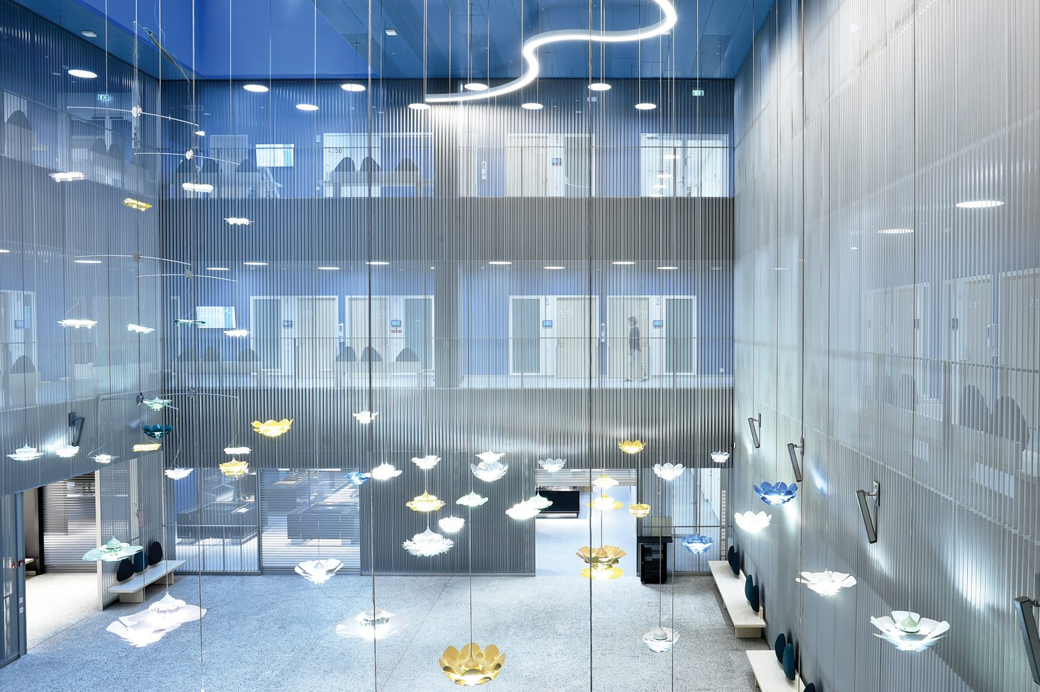 Suggesting jellyfish, Petri Vainio pendant fixtures hover from the ceiling in the cafeteria; photography: Studio Juha Sarkkinen.
