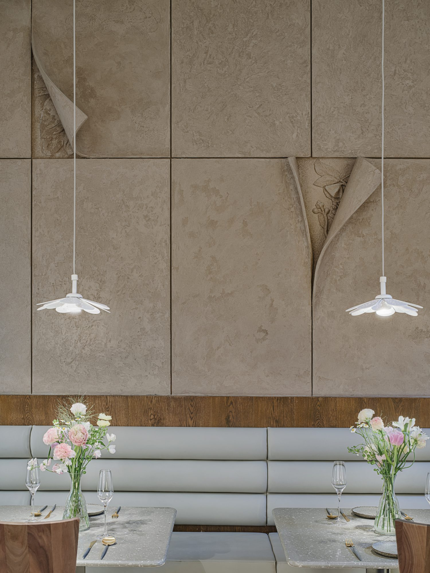 Blossoming white pendant fixtures illuminate tables. Photography by Jun Sun.