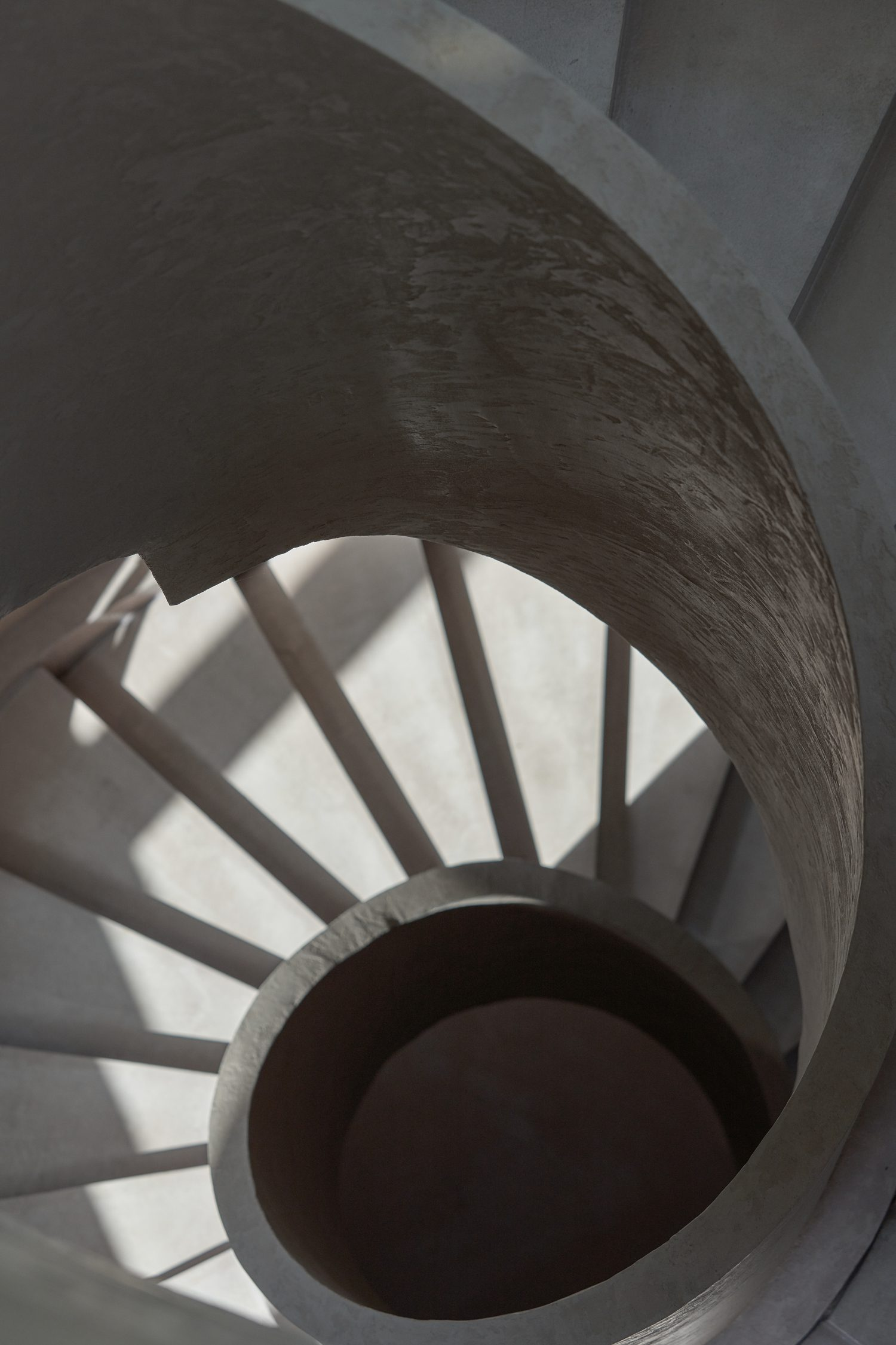 The microcement staircase leads to an upper level. Photography by Jun Sun.