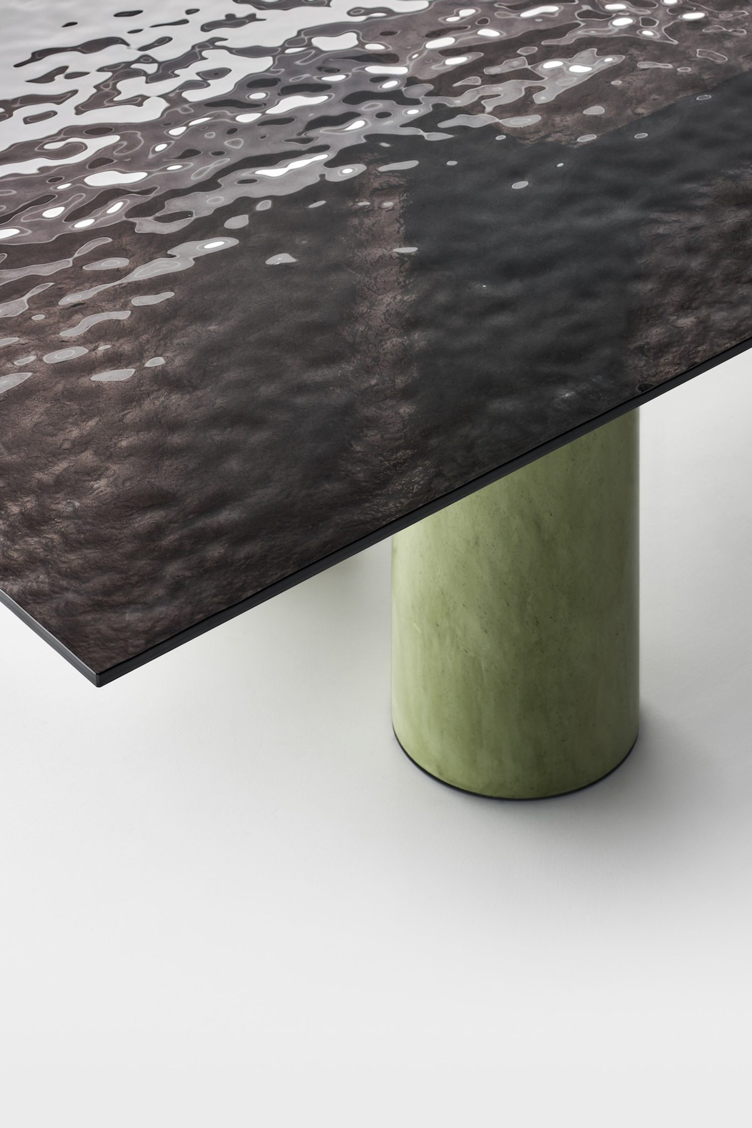 Close up detail of the glass top and green table leg.