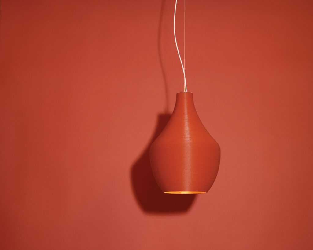 A red pendant light against a matching red background