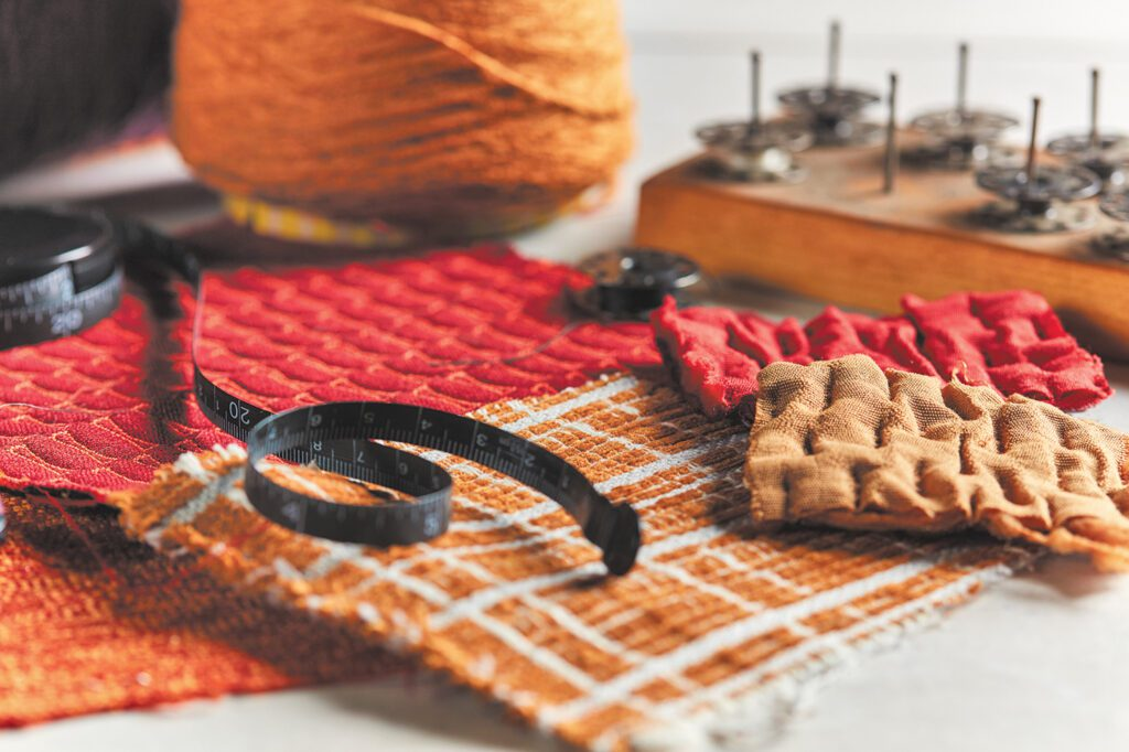 A collection of fabrics in reds, oranges and browns.