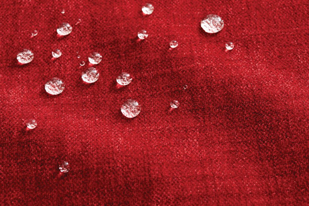A dark red fabric with drops of water sitting on top.