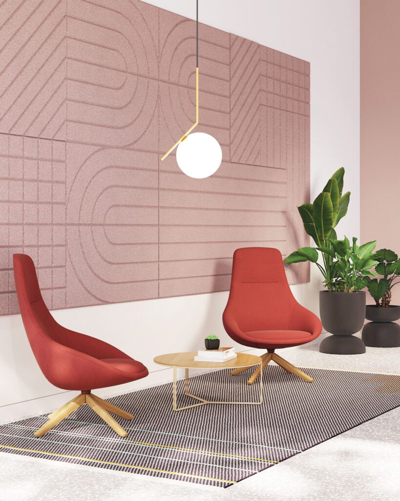 Two red fabric chairs sit in an entryway in front of a gray and red piece of art.
