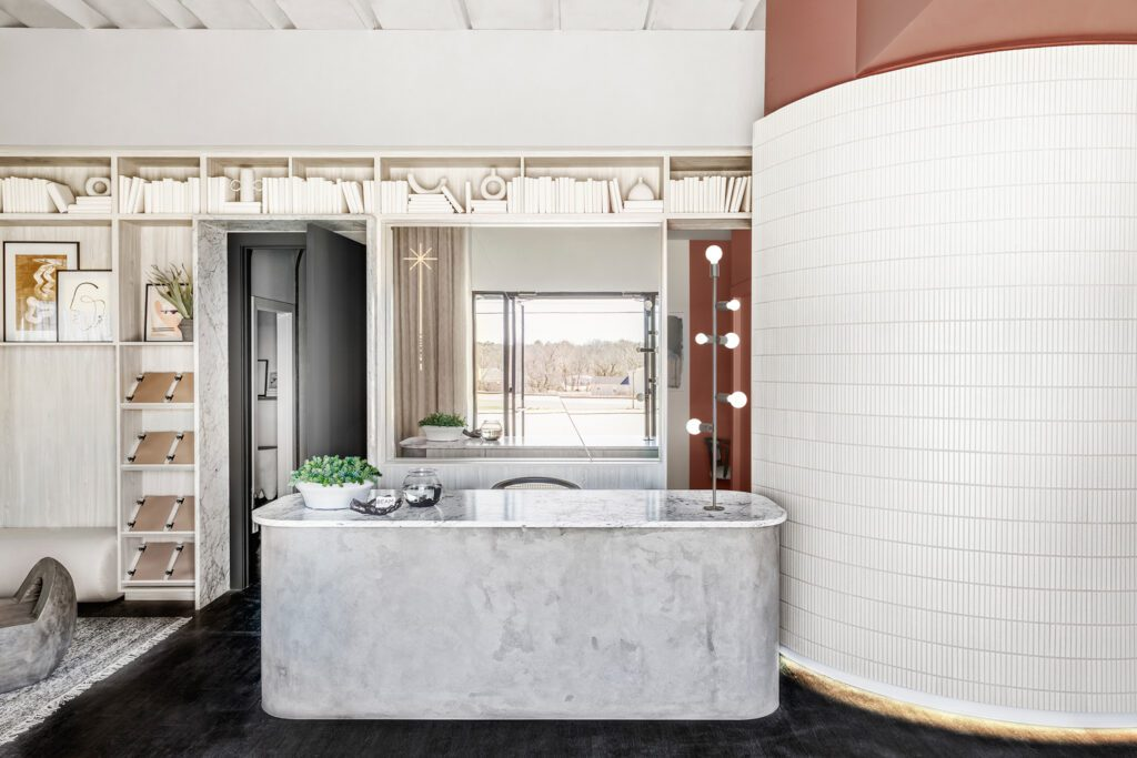 A reception desk topped in Carrara marble—and doorways lined in it—greet guests.