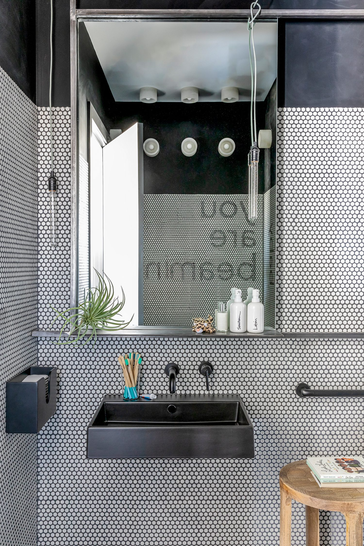 A bathroom, clad in Ann Sacks penny tile, offers wood toothbrushes.