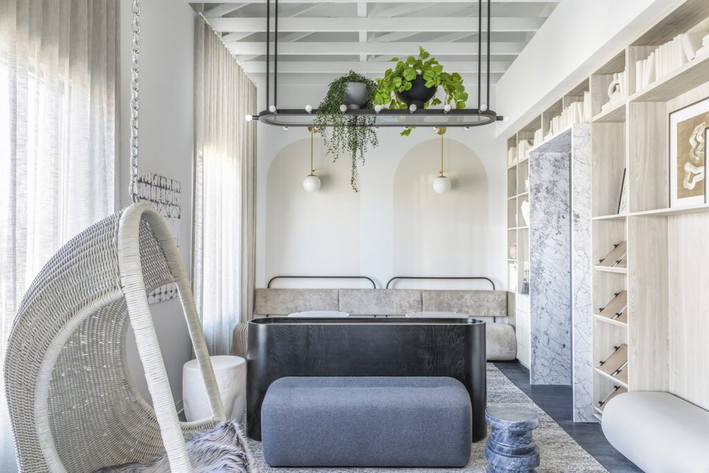 A waiting area for adult patients offers an Arteriors wicker hanging chair, Noir tables, a small bench upholstered in Carnegie fabric, and a longer bench by the wall upholstered in Holly Hunt's Great Outdoors.