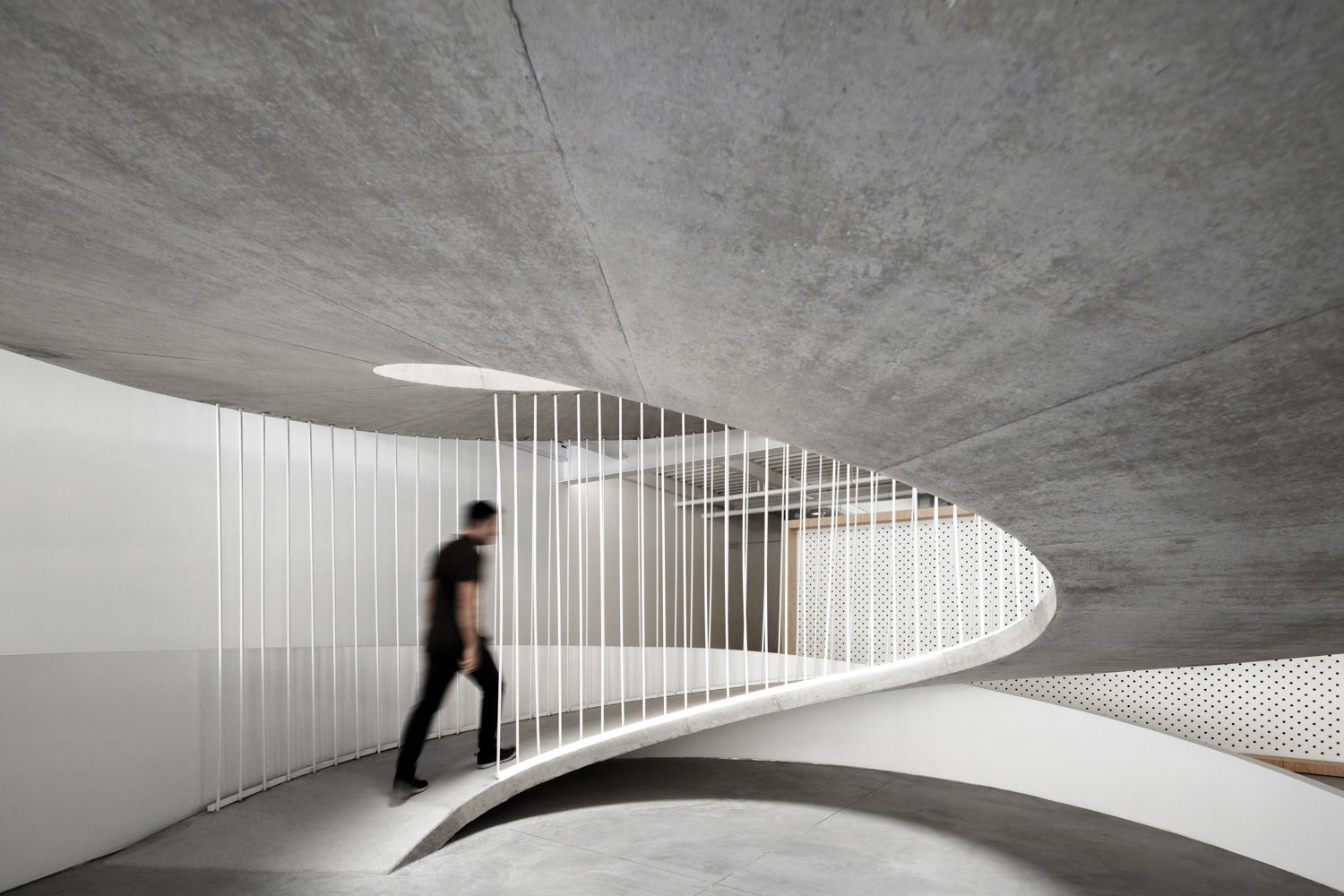 A 200-foot-long concrete ramp curls through the joint three-story offices of culinary communications agency Clavel's Kitchen and tech company E-goi in Matosinhos, Portugal, by Paulo Merlini Architects.