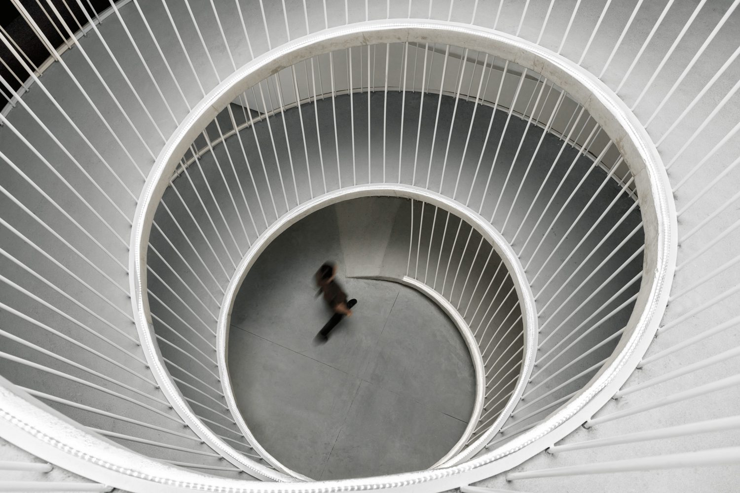 Lacquered iron tubes support the ramp from above as it winds through the office's three levels.