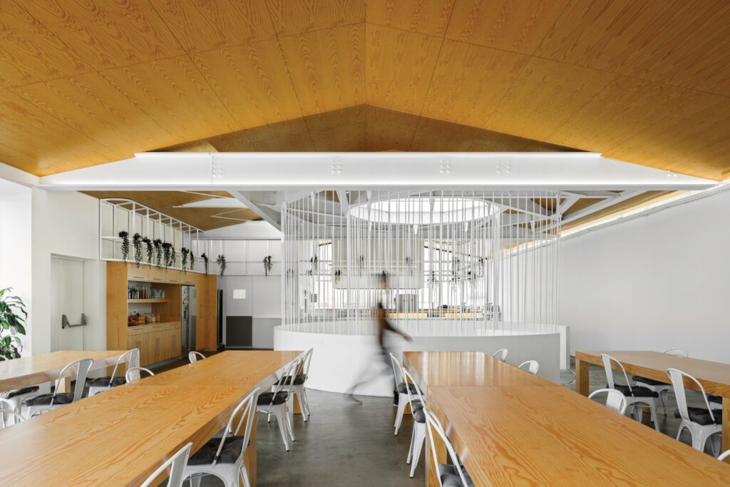 The employee café, with an oak ceiling and tables, is designed like a restaurant for potential leasing opportunities.