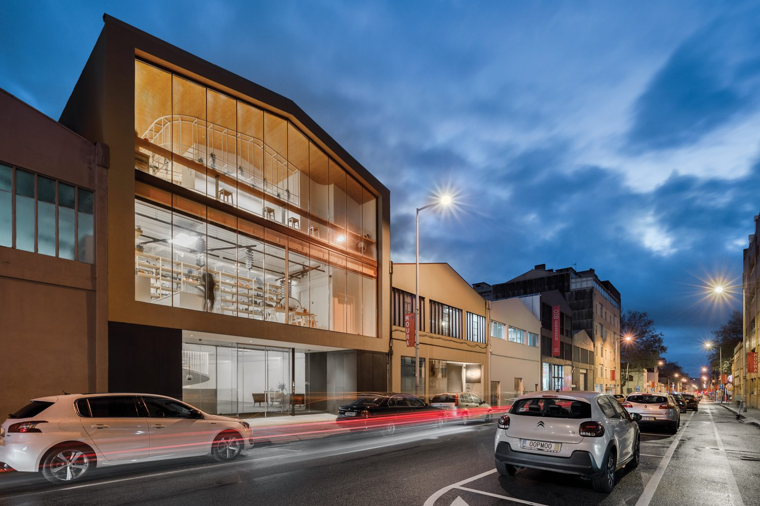City ordinances required that the new building match the height and pitched roofs of the surrounding warehouses, but extensive glazing allows passersby to view into the photo studio and café on the second and third floors.