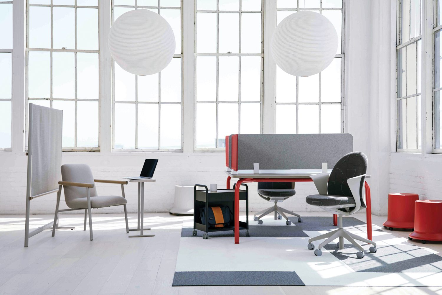 A bright office space making use of two red stools and a gray screen divider.
