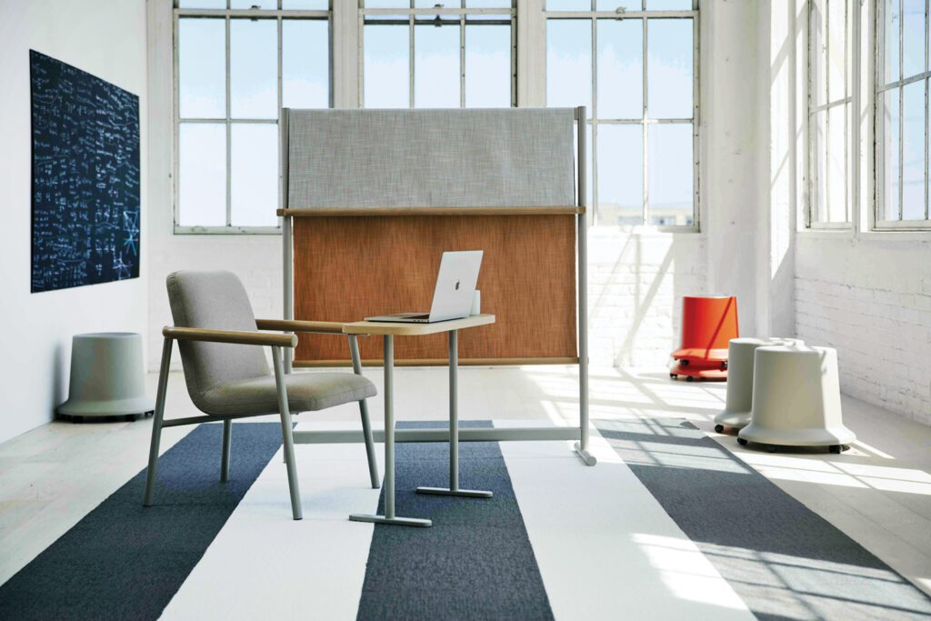 A bright office space making use of two stackable stools and a gray and brown screen divider.