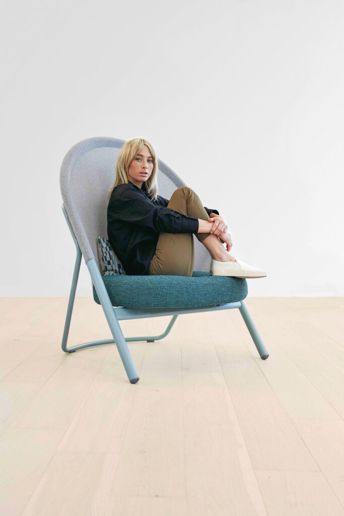 A woman sits in a blue and gray high-back chair.