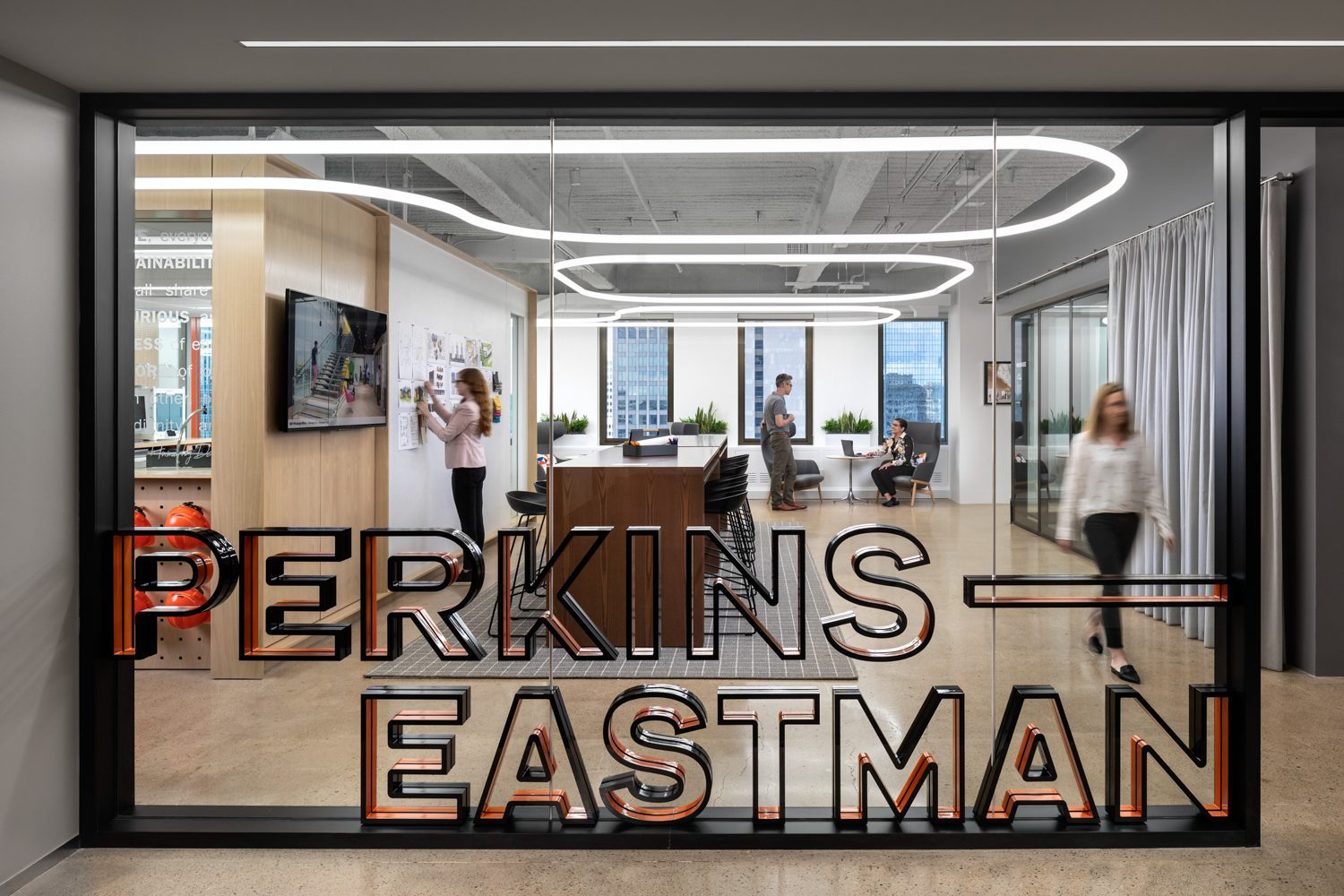 A black-and-orange framed logo affords views of the office.