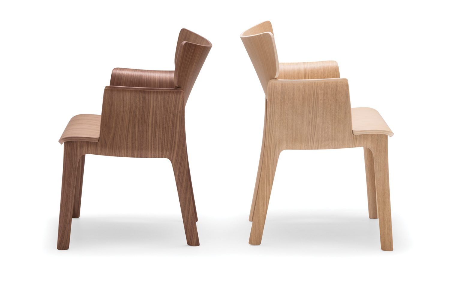 Two chairs, back to back. The one on the left is a dark brown and the other on the right is a light brown.