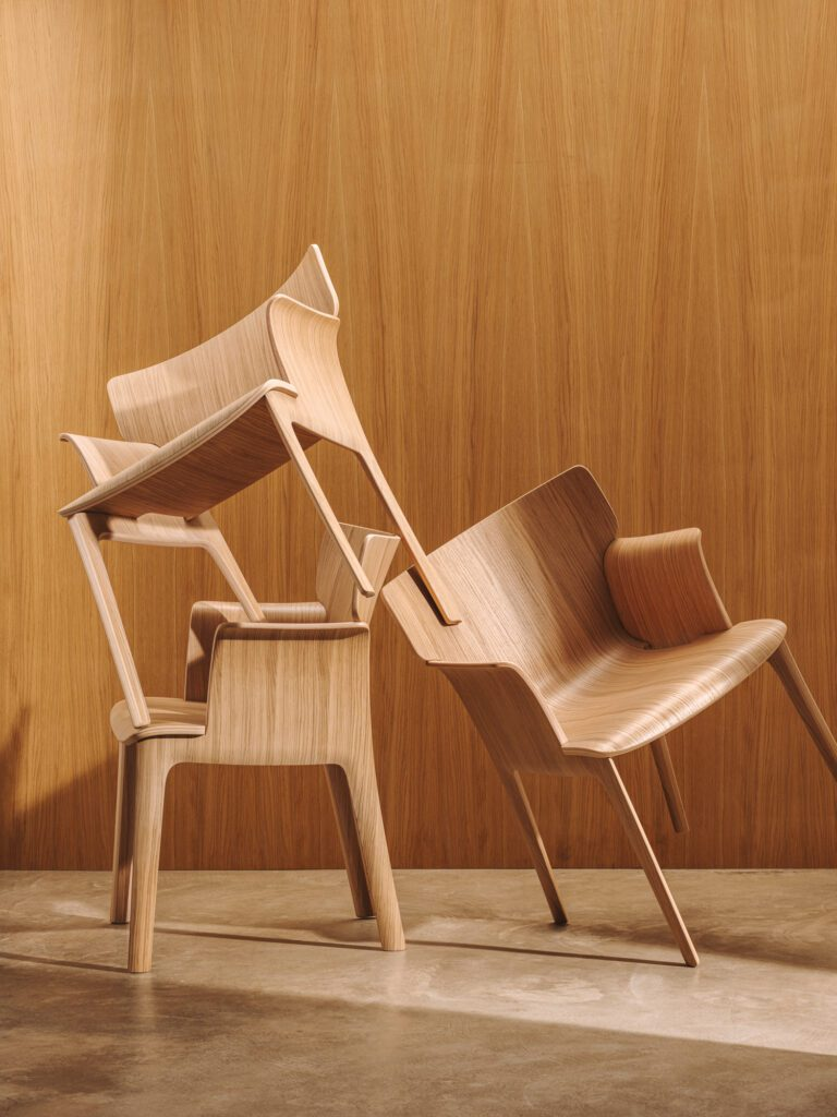 Two plywood chairs lean against each other while a third is stacked on top.
