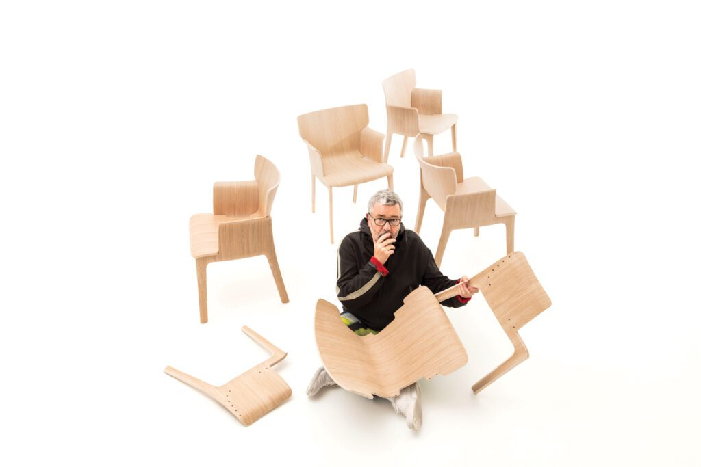Designer Philippe Starck pictured here with the plywood chairs he designed. He is holding one unconstructed chair, which is in three pieces: the sides with legs and the seat.