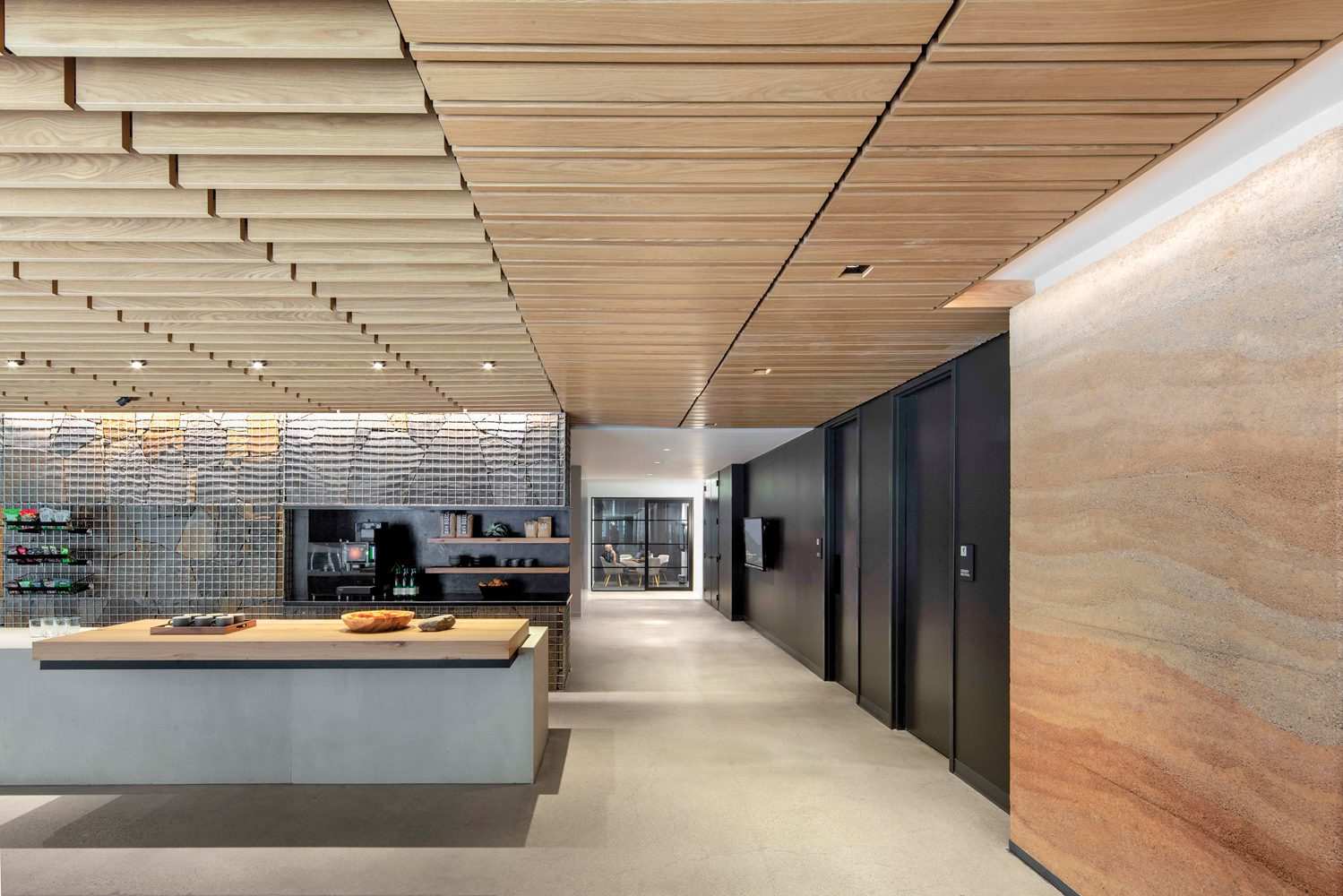 Rammed-earth paneling and a flagstone gabion wall frame the coffee bar.