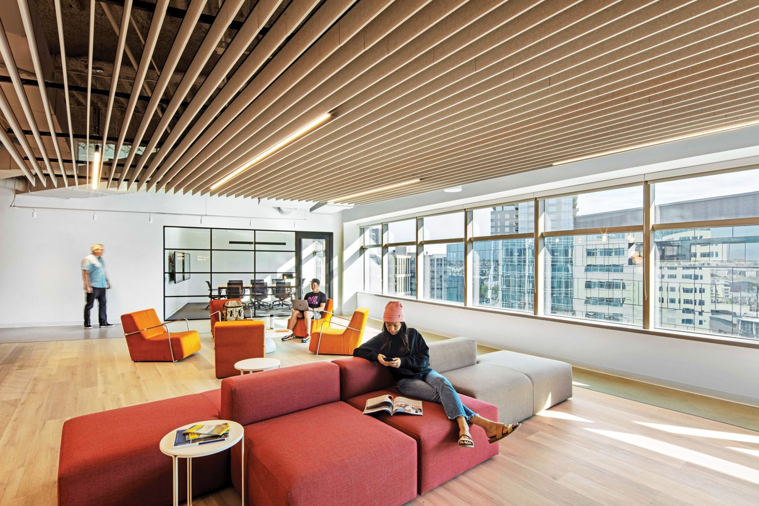 Acoustic polyester ceiling baffles hang above José Miguel Andrés chairs and more Yoom sofas in the penthouse lounge.