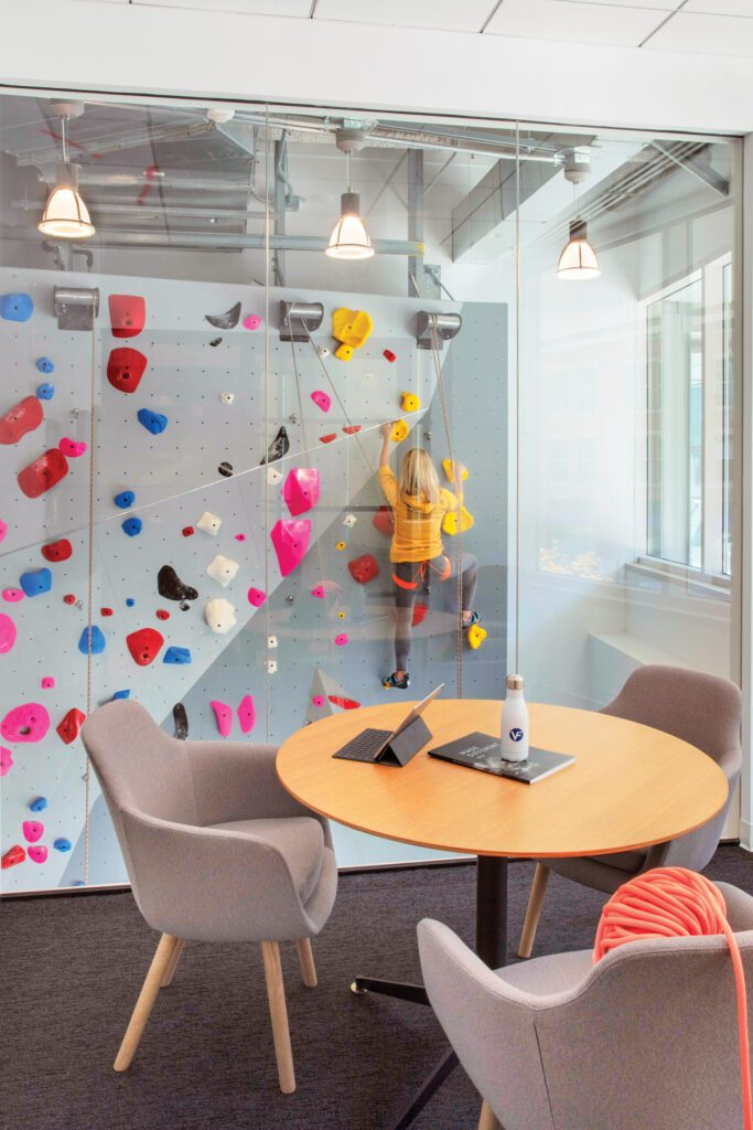 An interview room with a Jephson Robb table and Naoto Fukasawa chairs overlooks the climbing wall.