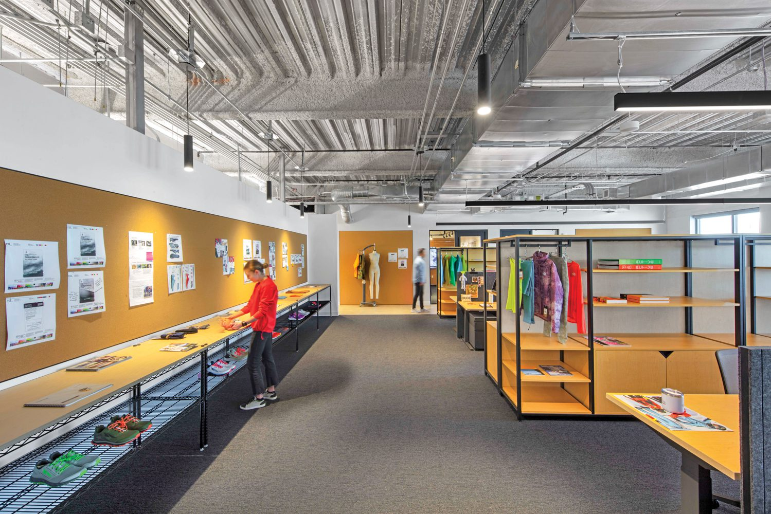 LED pendant fixtures illuminate tackable cork panels and maple plywood–topped storage units in a Smartwool office area.