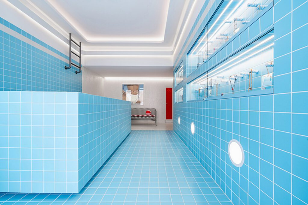 Shimmery turquoise ceramic tiles, rounded lights, a bench and red lockers further achieve a realistic swimming pool look.
