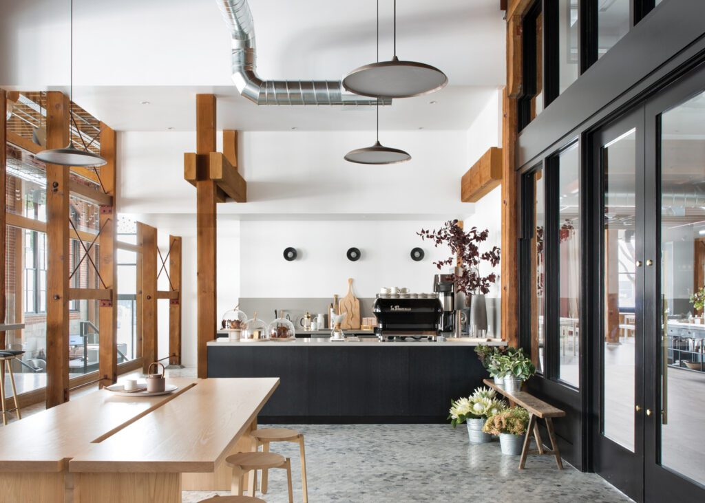 Reception adjoins a French bistro–inspired staff coffee bar with a custom white-oak communal table.