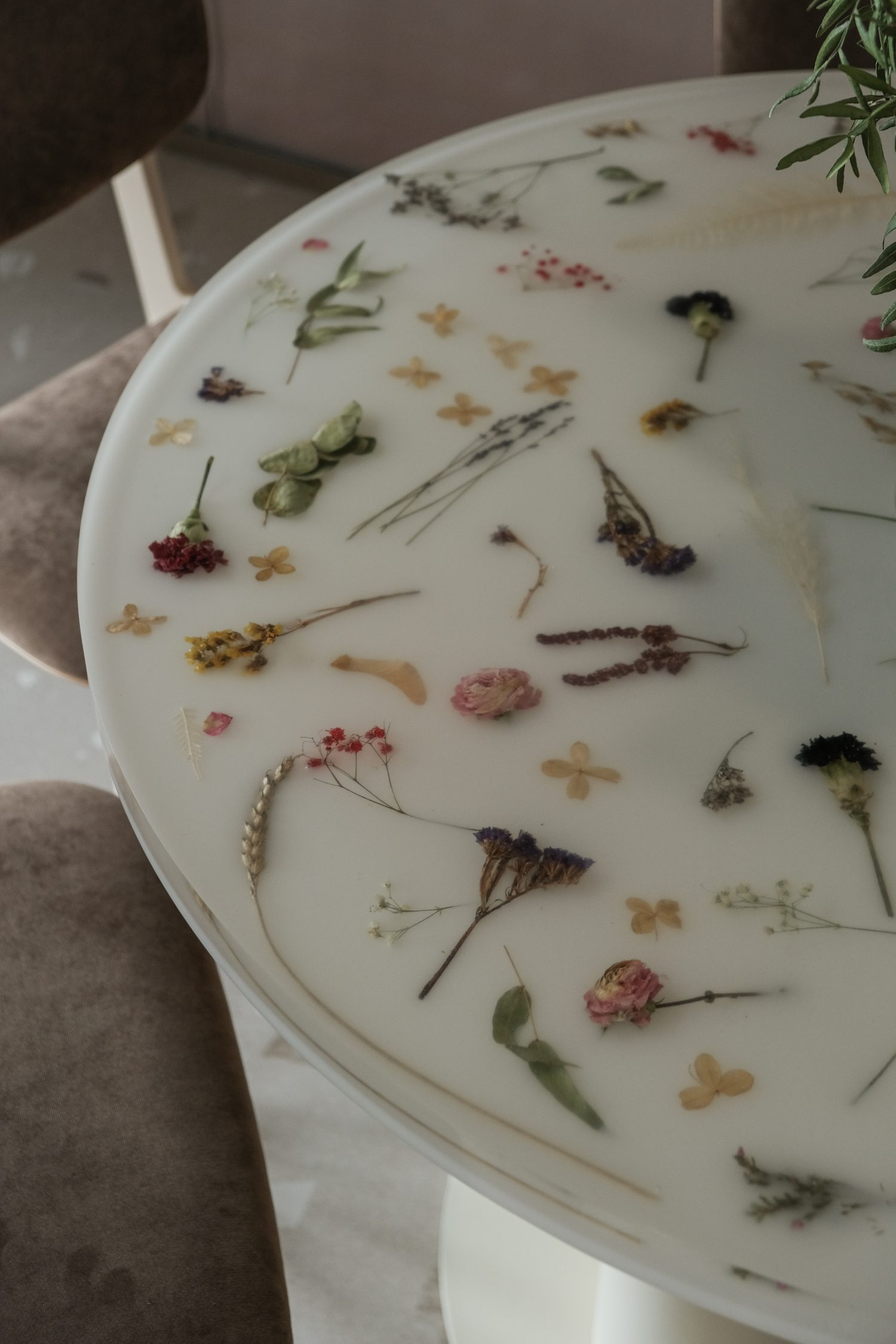 A circular tabletop offers the sweet surprise of embedded flowers.