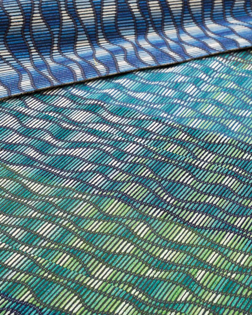 The Ora upholstery, pictured here, is a variety of blues and greens arranged in wavy lines.