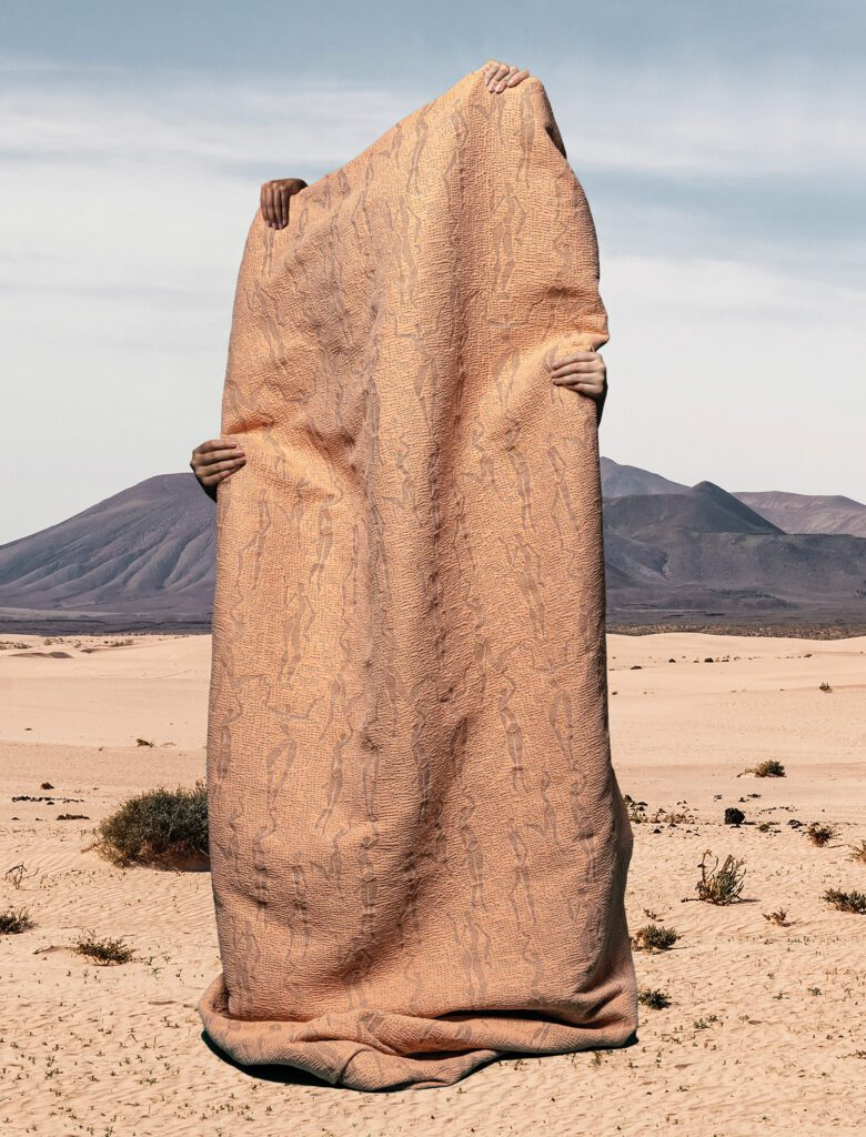 A tan fabric with gray body figures embroidered is pictured here, held by three hands, against a desert backdrop.