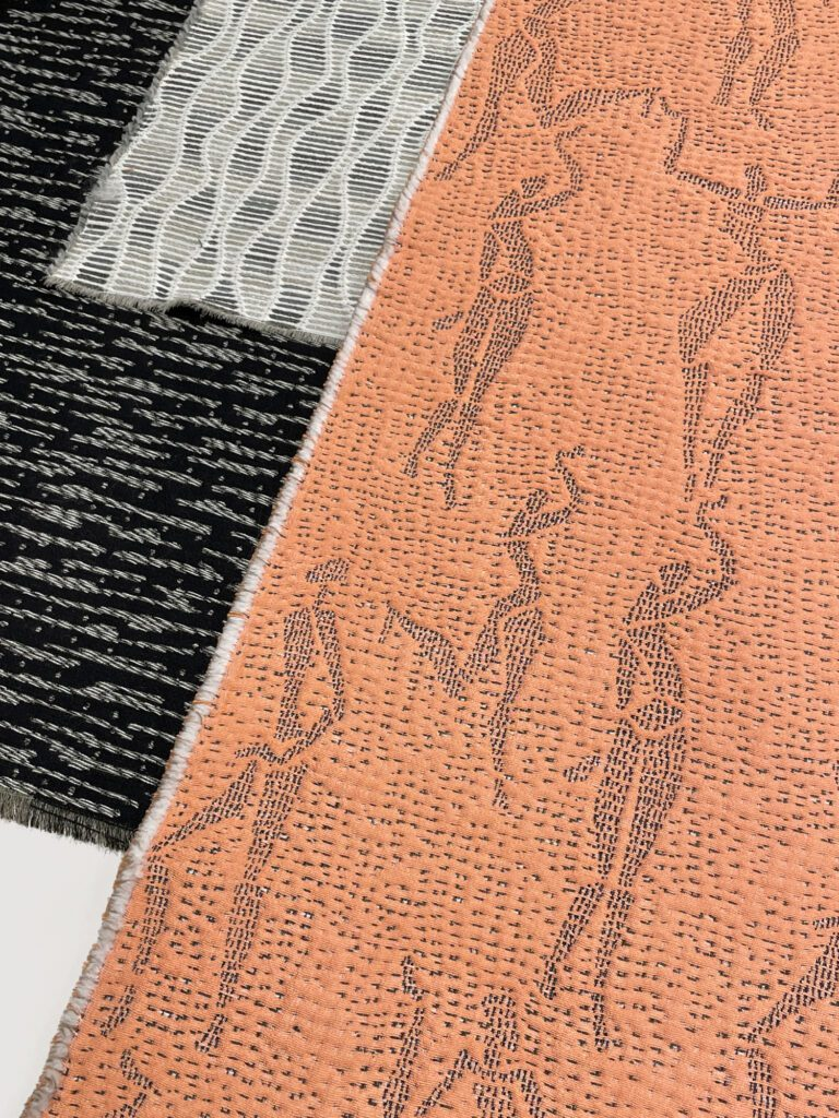 The Elena print upholstery is a peach colored fabric with gray body figures embroidered.