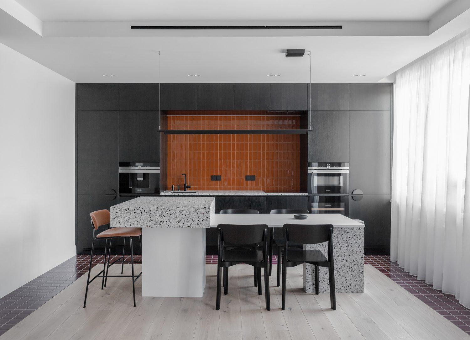 The wine tiles in the kitchen are mirrored in the living area, but in an inverse pattern.