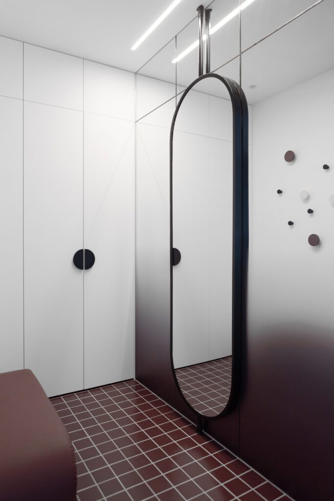 Like the floor-to-ceiling doors, this vertical mirror draws the eye upward, creating the illusion of height..