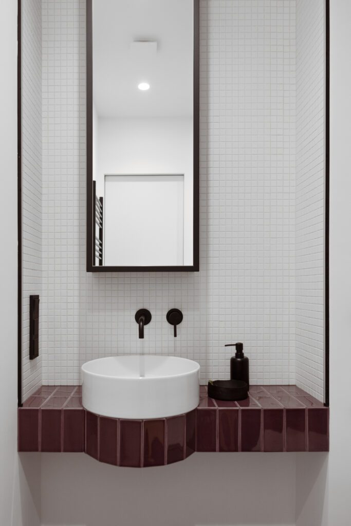 The bathroom console features a ledge for a round washbasin surrounded by tiles that match the floor.