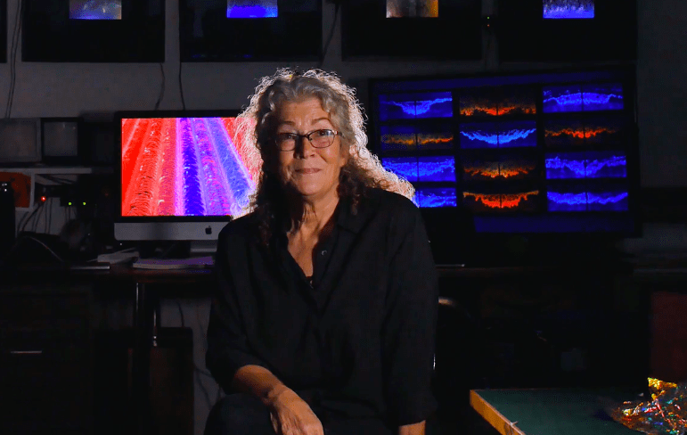 Lyn Godley sits in a dark room with glowing screens in the background.