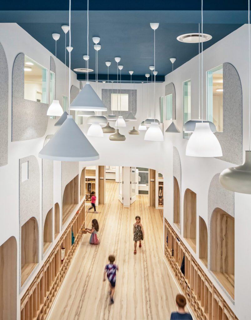 The double-height entryway of City Kids preschool in Williamsburg, its ceiling painted to evoke the night sky.