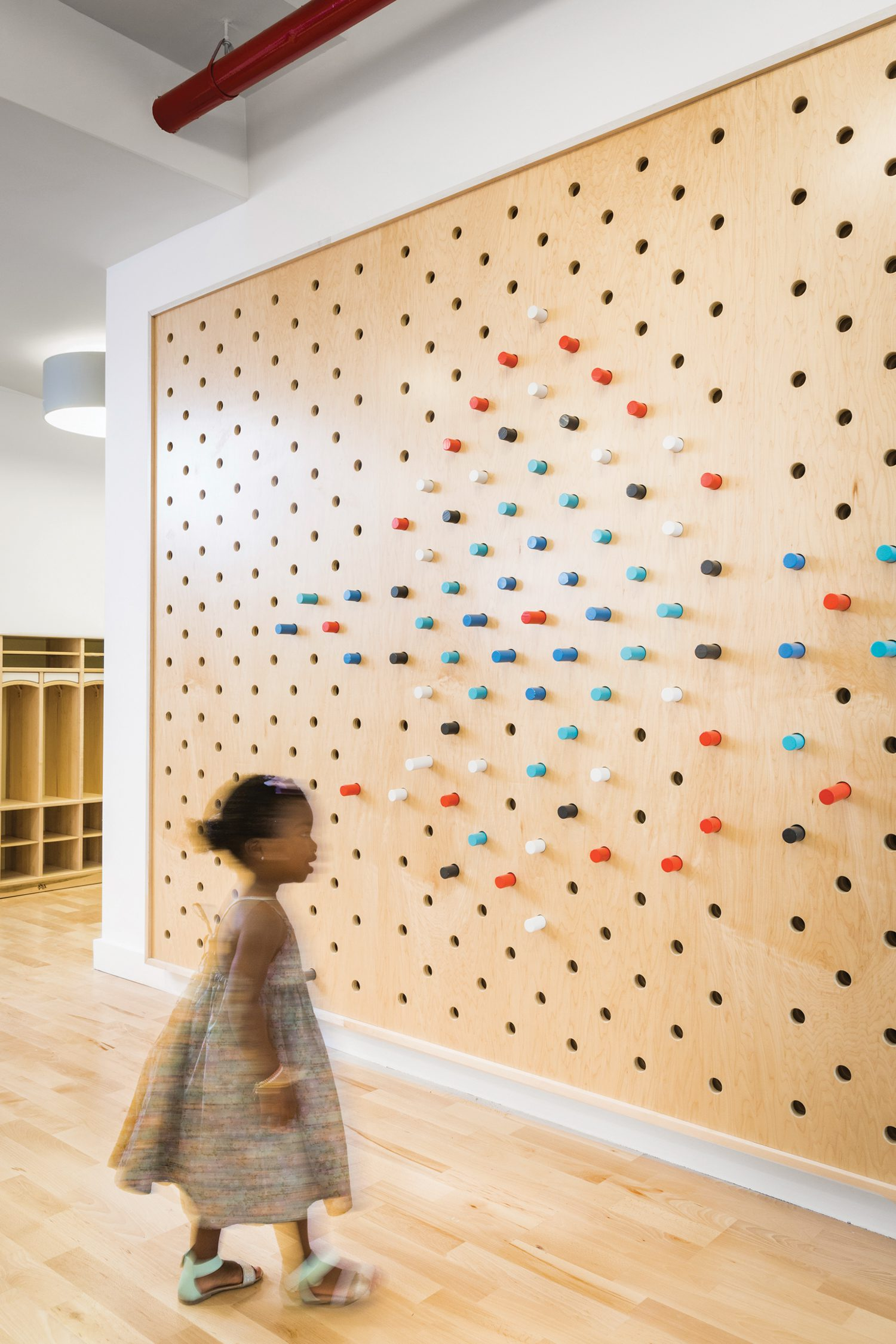 A pegboard feature wall serving a toddler's perspective at the Maple Street School in Prospect Lefferts Gardens, a collaboration with 4 MATIV.