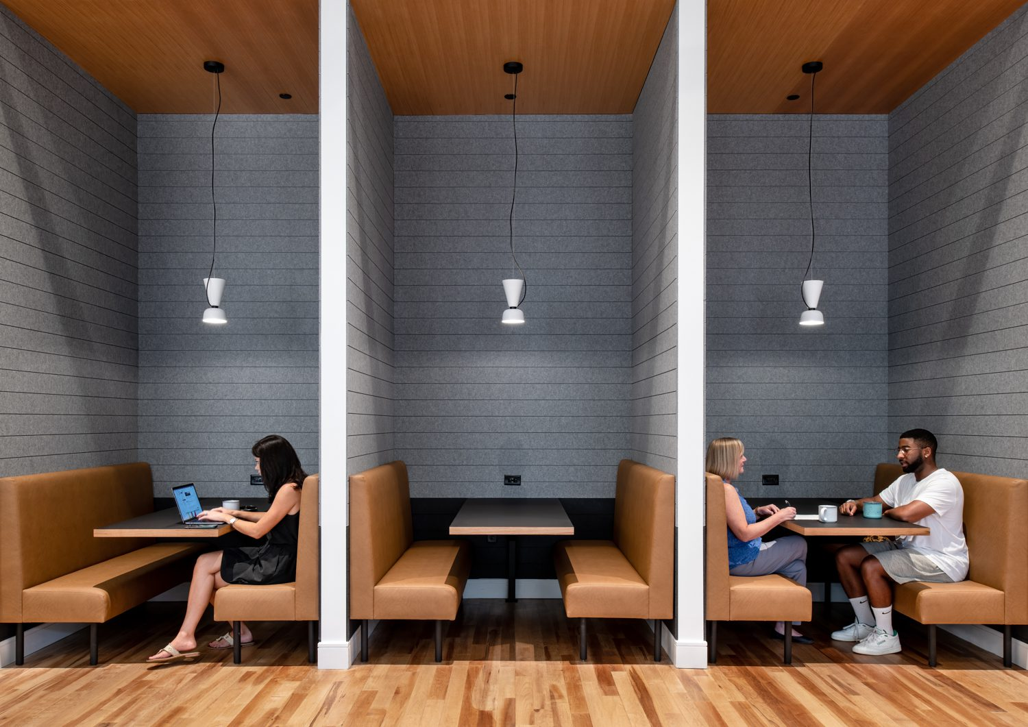 Just off the kitchen, Hem pendants hang over booths clad in custom Autex panels with seats upholstered by CF Stinson.