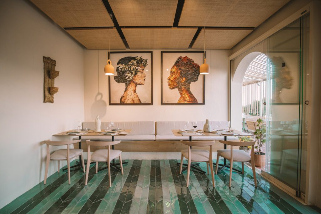 A sea-green installation of herringbone tiles defines a dining area.