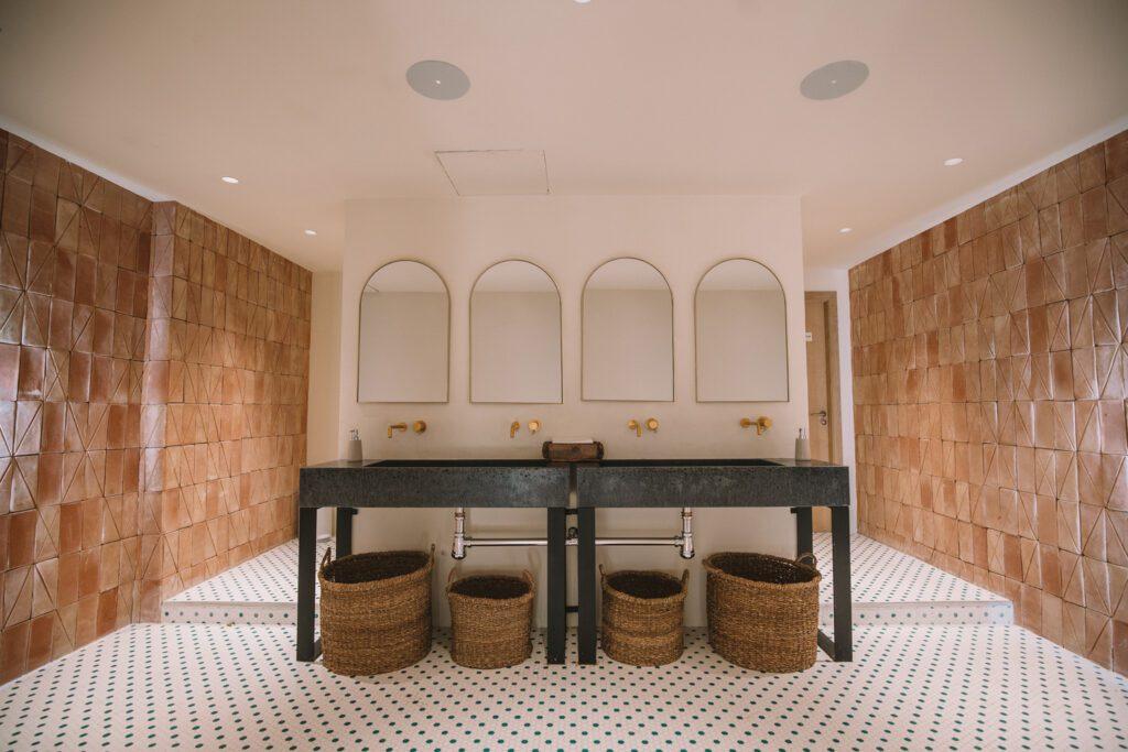 The bathrooms offer shared washbasins in a dark terrazzo.